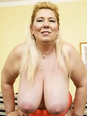 Mature lady is shaking her huge fat tits violently and fingering her pussy